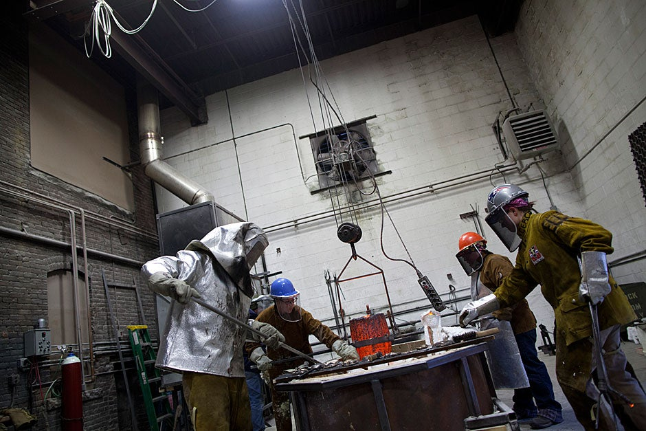 Faces covered by heat-resistant masks and bodies protected by heat-resistant jackets and thick leather gear, the foundry staff, including Derek Russell (from left), Shayla MacDonald, Marjee Levine, and Jesse Morrisey, move in concert, maneuvering the crucible toward the casting pit.  Stephanie Mitchell/Harvard Staff Photographer