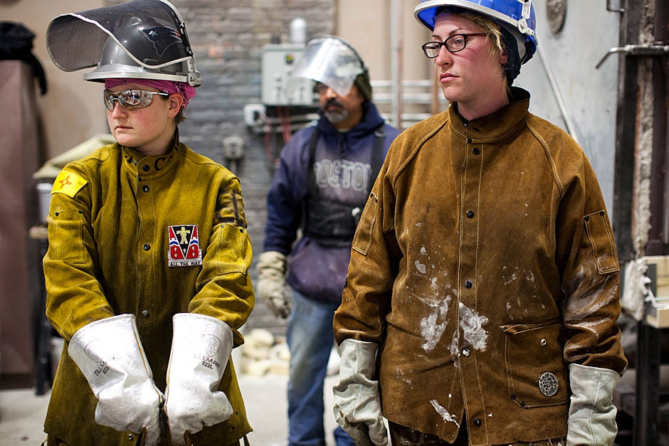 Jesse Morrisey (from left), Rafael Ramirez, and Shayla MacDonald, members of the foundry staff, wait for the second set of sculptures as the crucible is reheated with metal.  Stephanie Mitchell/Harvard Staff Photographer