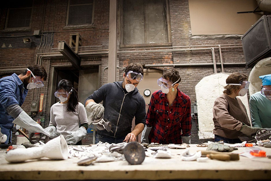 Students, including Adam Stack (from left), Michelle Chang '15, Daniel Zolli, Jordan Troeller, Kara Feilich, and Caitlin Henningsen, work in pairs to break away the ceramic shell from their medallions.  Stephanie Mitchell/Harvard Staff Photographer