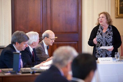 Harvard Board of Overseers president Leila Fawaz (standing), Issam M. Fares Professor of Lebanese and Eastern Mediterranean Studies at Tufts University, speaks to the board at a recent meeting at Loeb House in Cambridge. Seated (from left) are fellow Overseers Cristián Samper, director of the Smithsonian's National Museum of Natural History, Richard Meserve, president of the Carnegie Institution for Science, and Robert Shapiro, partner at the law firm Ropes & Gray.