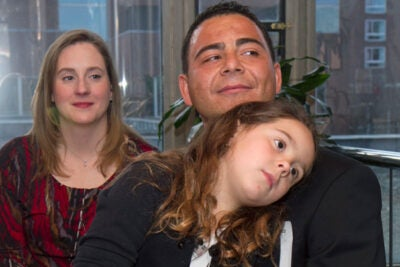 Ronaldo Antunes (right) was among the 23 Harvard staff members who celebrated their U.S. citizenship. Antunes was joined by his daughter Madeleine, 7, and wife Michele.