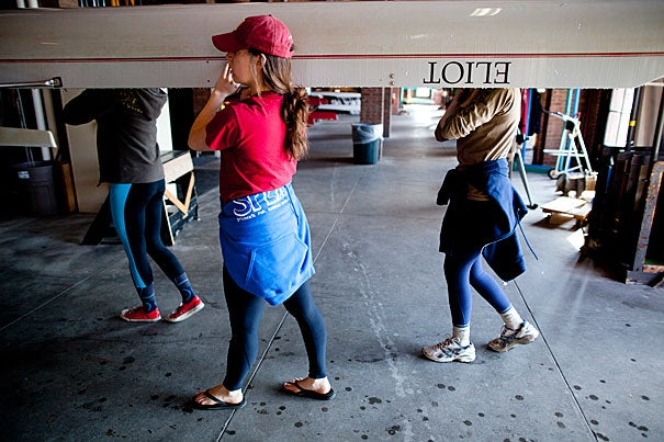 Eliot House residents in the Eliot Boat Club, the intramural crew program, haul their boat to the Charles for a morning row.