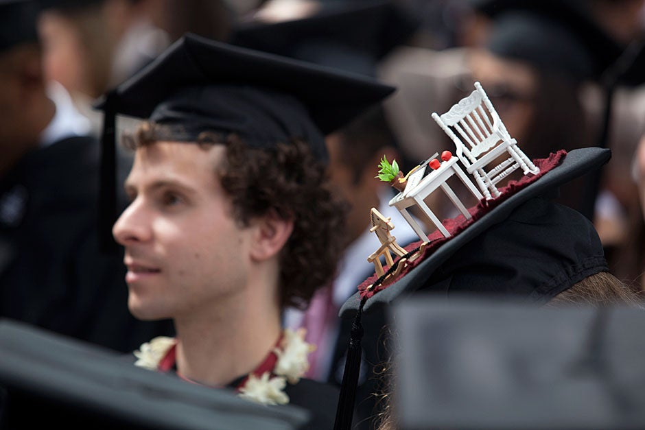 Next to a hat featuring a room with a view, Matt Aucoin '12 watches the ceremony. Kris Snibbe/Harvard Staff Photographer