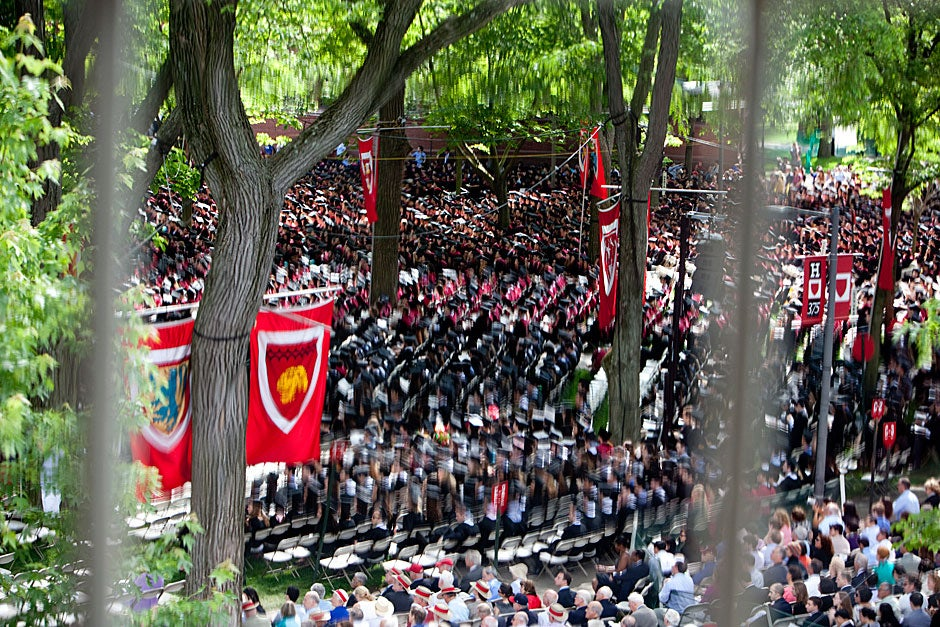 Flags and graduates seen through the leaded glass of University Hall.  Rose Lincoln/Harvard Staff Photographer