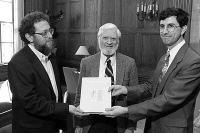 """Horace Gray Lunt (center), the Samuel Hazzard Cross Professor of Slavic Languages and Literatures Emeritus, is pictured with a copy of """"The Slavonic Book of Esther."""" Lunt spearheaded a golden age of Slavic studies."""