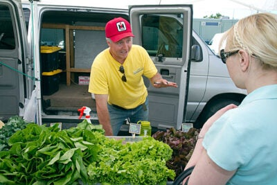 Frank Ventura of Dragonfly Farms speaks to a customer at the Harvard Allston Farmers' Market, which kicked off the season last week and will continue running Fridays, 3-7 p.m. The Cambridge market takes place Tuesdays from noon to 6 p.m. in front of the Harvard Museum of Natural History.