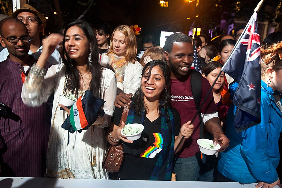 Jasdeep Randhawa '13 (left) and Divya Dhar '13 (center) are all smiles as they finally get served ice cream after a long wait during Harvard's 375th anniversary celebration in Tercentenary Theatre. Jon Chase/Harvard Staff Photographer