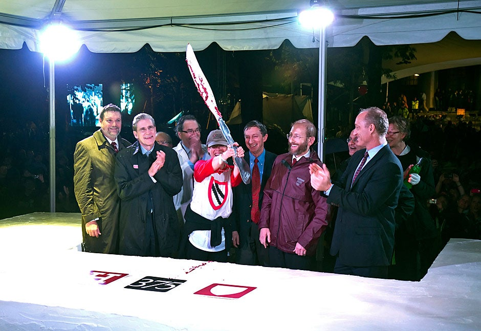 Lizabeth Cohen, Howard Mumford Jones Professor of American Studies and dean of the Radcliffe Institute for Advanced Study, holds a giant knife aloft after cutting the cake during the 375th anniversary celebration in Tercentenary Theatre. Jon Chase/Harvard Staff Photographer