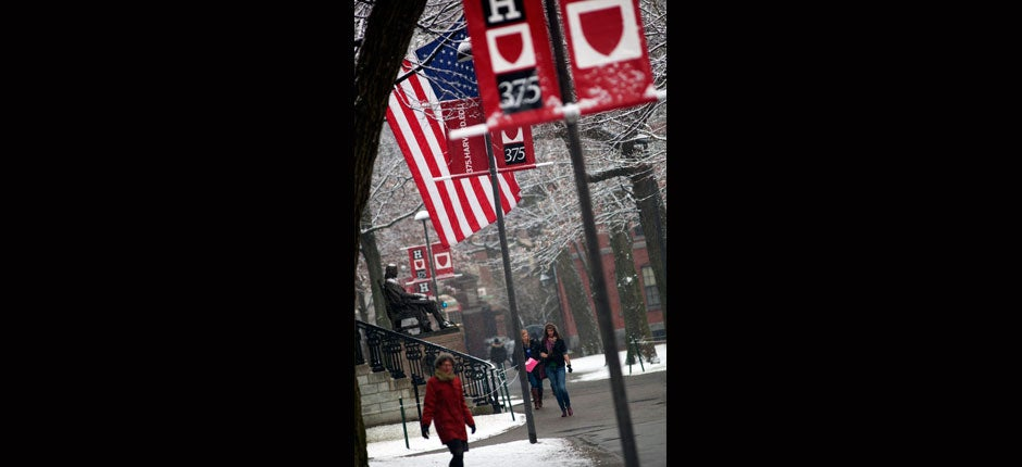 Snow falls on the John Harvard Statue while 375th signs decorate Harvard Yard. Kris Snibbe/Harvard Staff Photographer