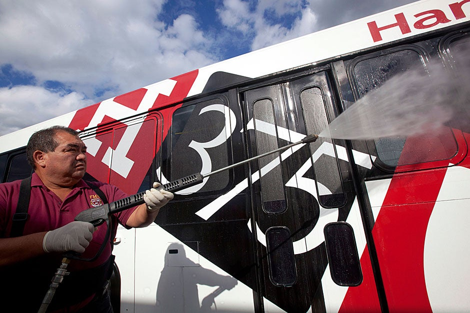 Miguel Espejo, from Harvard Custodial Services, uses rainwater to wash Harvard Shuttles decorated with the 375th logo. Kris Snibbe/Harvard Staff Photographer