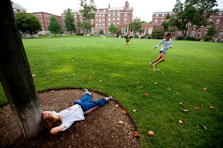 Sol (from left), age 6, the son of resident dean Jill Constantino, relaxes under a tree while the children of Cabot House Masters Rakesh and Stephanie Khurana, Jai, age 9, and Nalini, age 12, have an impromptu running race on Radcliffe Quadrangle on move-in day at Harvard University. Rose Lincoln/Harvard Staff Photographer