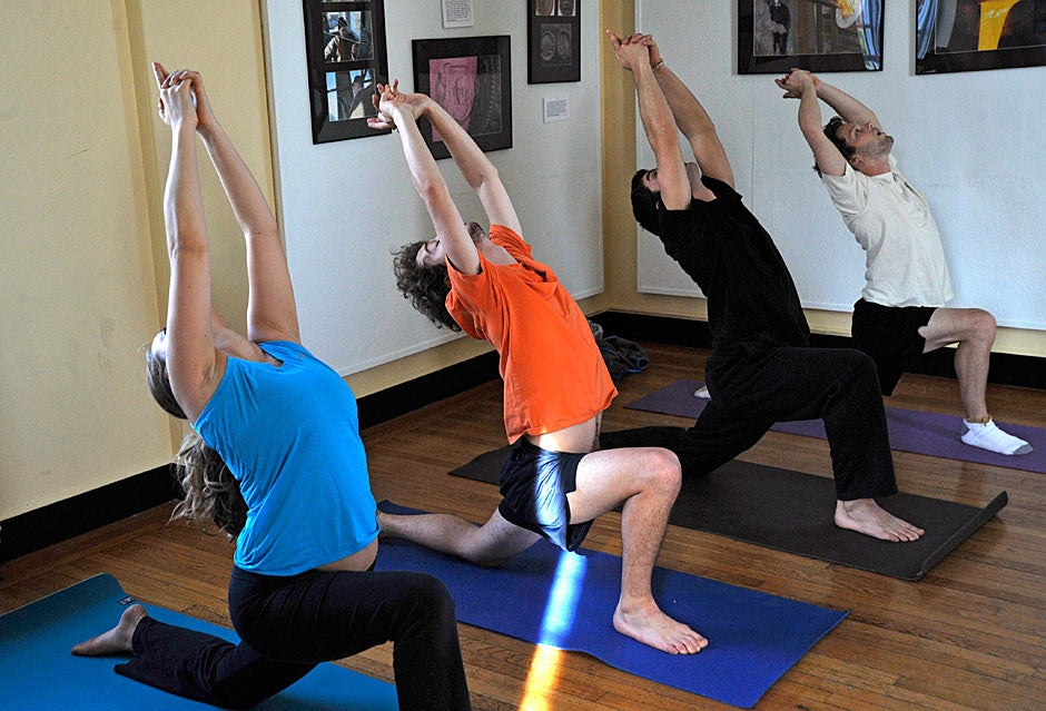 Shaomin Chew '13 leads a yoga class in the Lowell House Tower Room. Katie Sylvan '13, Eli Martin '13, Jerry Tullo '12, and Johnny Motley '12 hold a pose. Jon Chase/Harvard Staff Photographer