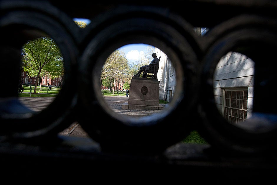 An orbicular wrought iron railing hugs the John Harvard Statue in Harvard Yard. Kris Snibbe/Harvard Staff Photographer