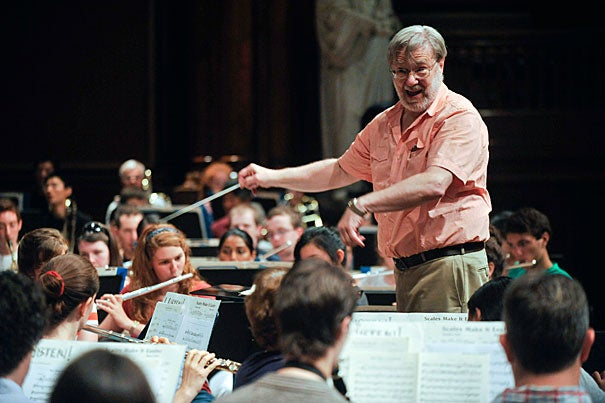 Tom Everett, director of bands at Harvard, takes the Harvard Summer Pops Band through its paces at Sanders Theatre. The band is celebrating its 40th anniversary with a concert in Harvard Yard on July 26.