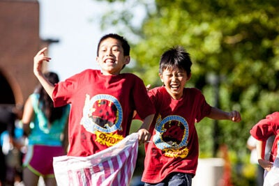 Eric Lin and Timmy Chen of Phillips Brooks House Association's Chinatown Adventure sack race with gusto at the association's midsummer celebration in Jamaica Plain.