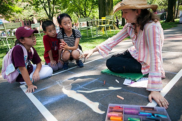 Shannon Liu (from left), Daniel Yang, and Cindy Yang (all visiting from Hong Kong) watch as Jerrie Lyndon, a sidewalk chalk artist, creates an Olympic-inspired drawing at an ice cream social held on Friday for Harvard staffers looking to beat the summer heat and get into the Olympic spirit.