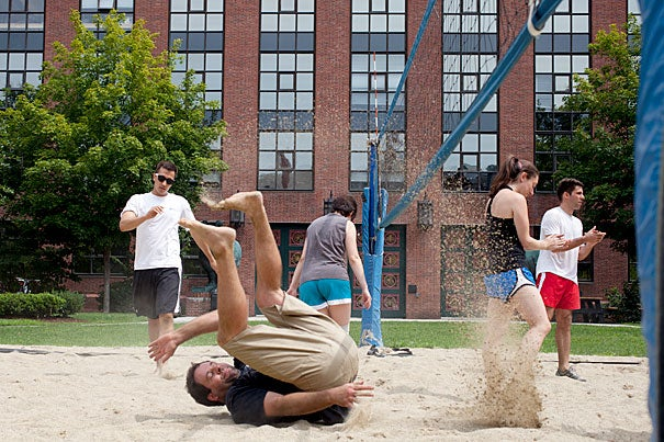 Nick Kuperwasser somersaults in the sand after making the shot at the summer Rhino Cup volleyball game. The annual Rhino Cup volleyball league stokes the competitive fires of Harvard's biological community, drawing researchers out of the lab and onto the sandy volleyball court at the Biological Laboratories. The finals are Aug. 29.