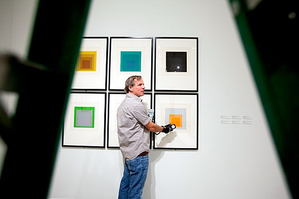 """Edward Lloyd, exhibitions manager at the Carpenter Center, checks the lighting on a series of works by Josef Albers, """"Homage to the Square,"""" which are included in """"circa 1963."""" The exhibit features works by 15 artists in vogue during the years of vinyl dinette sets, the Kennedy White House, and airplanes with ashtrays."""
