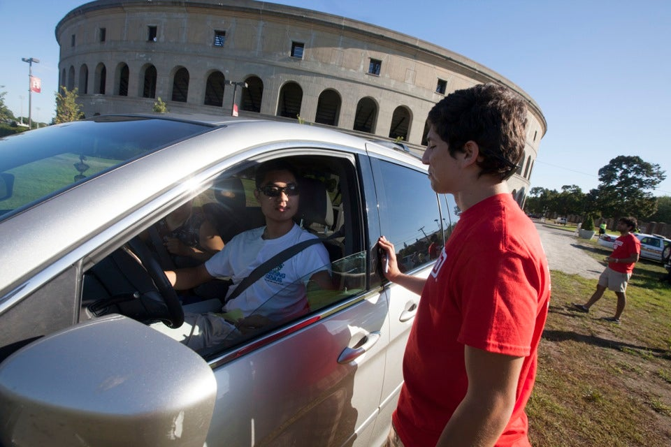 Kevin Hernandez `13 greets Jack Huang `16 (left) at Harvard Stadium as cars line up to enter Harvard Yard for the annual tradition of Move-In Day.