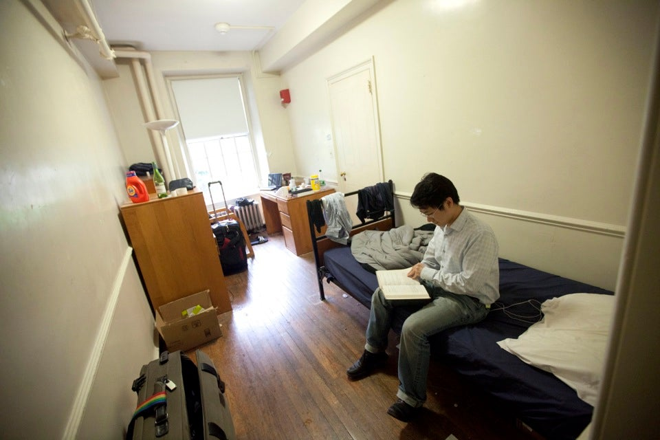 Framed by the doorway to his bathroom, Luchen Wang `14 studies in his Old Quincy House dorm before the renovation.  Wang's roommate had to pass through Wang's room to get to the bathroom and Wang needed to pass through his roommate's room to leave the dorm. The new configuration is more spacious and provides more privacy.