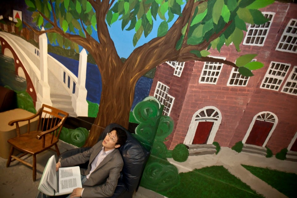 Luchen Wang `14 lounges in front of a student mural depicting Quincy House and the Weeks Bridge in the basement of Old Quincy prior to renovations.