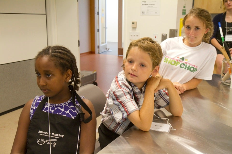 Students (from left) Rith Shiferaw, 9, Peter Murphy, 9, and Chkloe Rosen, 17, sit in a science and cooking lab at Harvard Listening to Somerville cheesemaker Lourdes Fiore Smith describe how to make string cheese.  Jon Chase/Harvard Staff Photographer