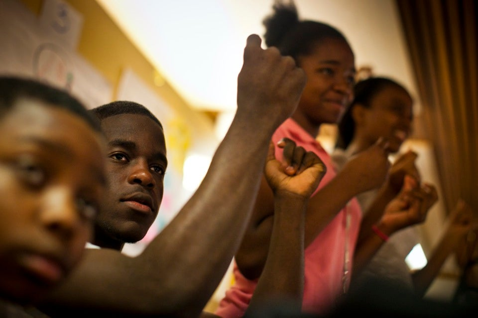 """Kurt Chadderton of the Health Careers Academy gives """"snaps"""" to fellow Crimson Scholars performing at the poetry slam.  Photo by Dominick Reuter Boston and Cambridge teenagers celebrate the end of a fruitful summer working at Harvard.  Harvard programs, departments, and Schools employed more than 150 local teens this summer. Kris Snibbe/Harvard Staff Photographer"""