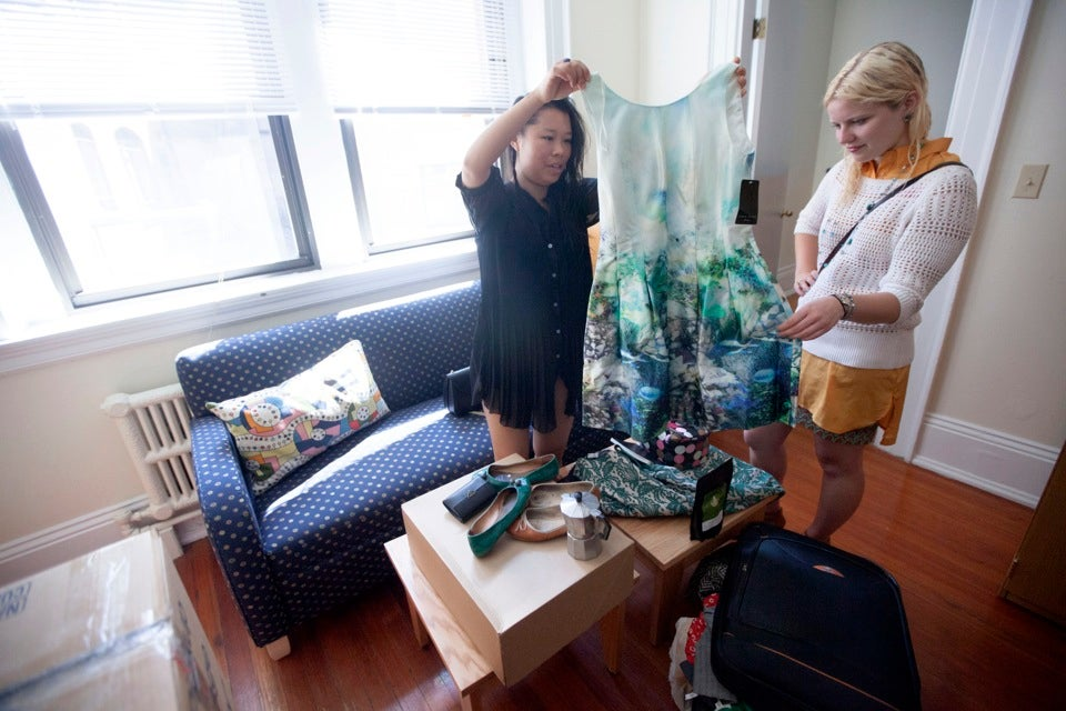 Inside Hampden Hall, Wendy Chen `14 (left) sorts through clothes with friend Michelle Timmerman `13, who lives next door in Adams House.