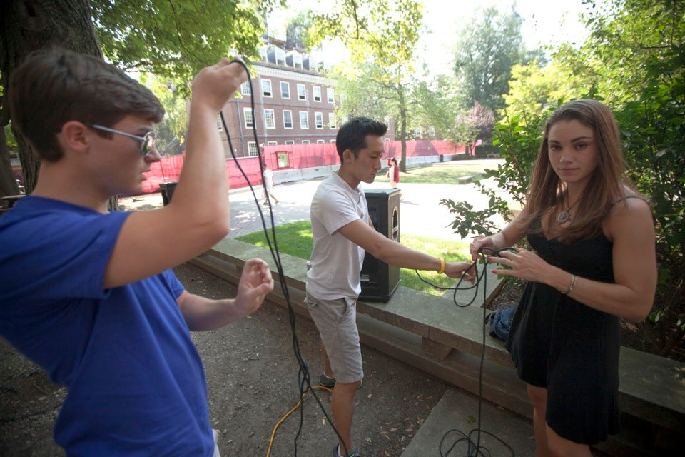 Matt Tufano `13 (from left), Scott Yim `13, and Christine Hughes `13 set up sound equipment for a Quincy House welcome-back barbecue.