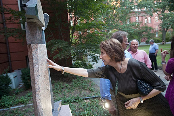 "Cynthia Hadzi admires ""Gilgamesh,"" a sculpture made by her late husband, Dimitri Hadzi, during the dedication ceremony in the courtyard by Tozzer Library. ""We'd always held onto it as a favorite of his,"" she said of the statue. ""I felt it needed to be seen by more people."""