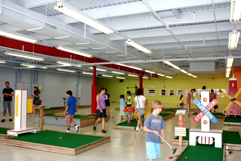 Allston-Brighton residents try their hand at educational mini-golf in the Harvard Allston Education Portal's new annex.  The Ed Portal offers mentoring in science, math, and writing, as well as community programming and activities year-round.  Vinay Devadanam/Harvard Public Affairs & Communications