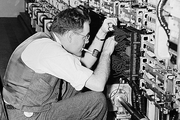 Harvard technician Robert L. Hawkins working on the Mark I multiply-divide unit during its installation in the Cruft Laboratory at Harvard University, Feb. 1, 1944.