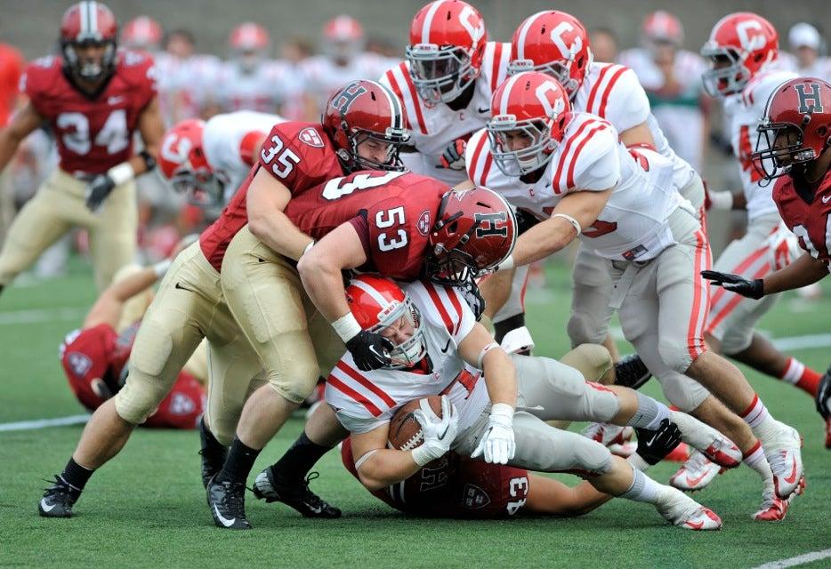 Crimson linebackers Bobby Schneider `13 (far left) and Connor Loftus `14 converge on Cornell wide receiver Grant Gellatly.