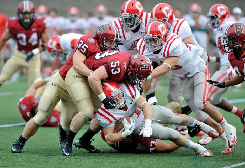 Crimson linebackers Bobby Schneider `13 (far left) and Connor Loftus `14 converge on Cornell wide receiver Grant Gellatly.