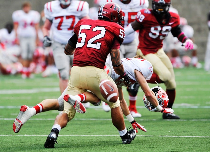 Crimson linebacker Joshua Boyd `13 (center) separates Cornell receiver Jesse Heon from his helmet and the ball after a particularly hard hit.
