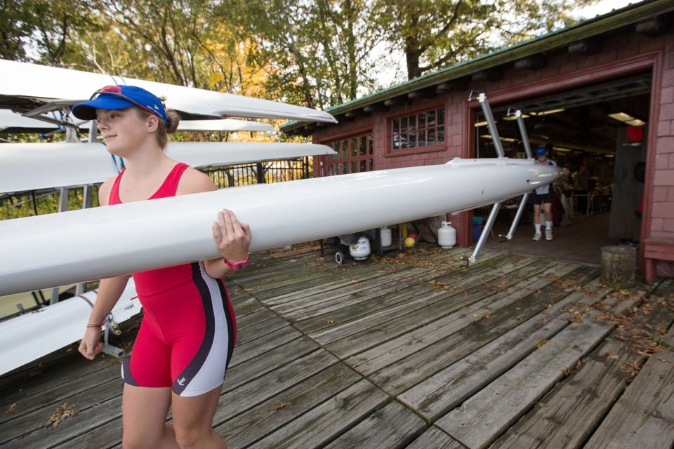 Winsor School student Abigail Parker and her father, Harry Parker, head coach of the Harvard men's heavyweight crew, bring their boat out of Newell Boat House. The duo participated in a Directors' Challenge doubles race composed of parent-child teams.