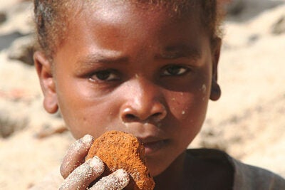 """A child holds a piece of """"vato malemy,"""" a river sediment that is consumed and is believed to have curative properties for gastro-intestinal illness."""