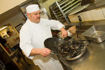 Mussels harvested on the shores of Prince Edward Island are among the sustainable seafood choices used by Harvard University Dining Services. At Leverett House, Ray Liberge creates a dish using the mussels. Jon Chase/Harvard Staff Photographer