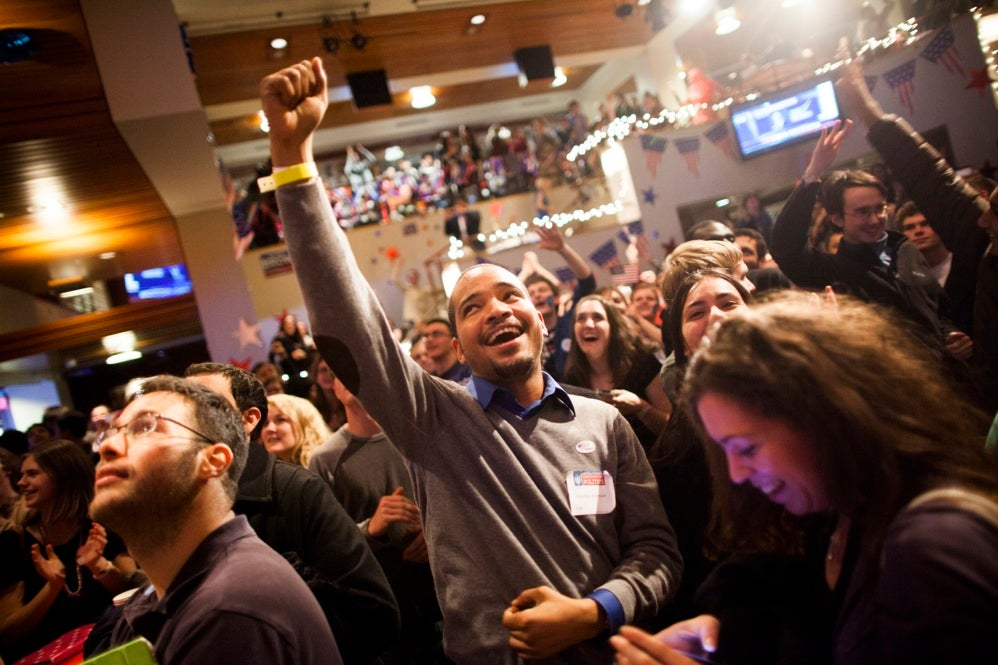 Students, faculty, and community members gather together in the Harvard Kennedy School JFK Jr. Forum to watch the election results. Maurice Anderson MPP2 (center) cheers as the presidential election results near the end. Stephanie Mitchell/Harvard Staff Photographer