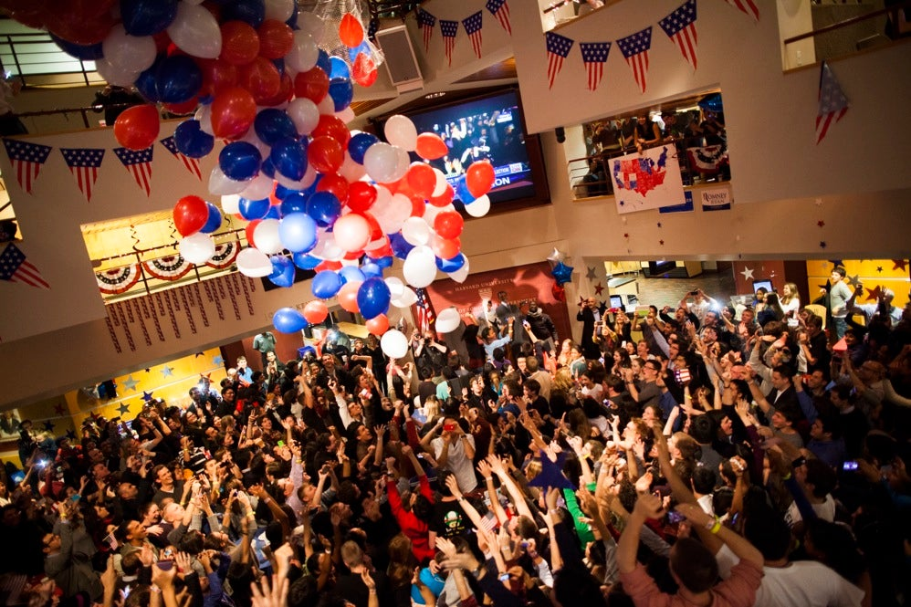Students, faculty, and community members gather together in the Harvard Kennedy School JFK Jr. Forum to watch the election results. Balloons fall on the crowd as the presidential winner is announced. Stephanie Mitchell/Harvard Staff Photographer