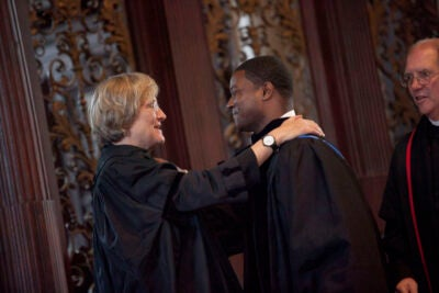 "Harvard President Drew Faust installs the Rev. Jonathan Walton as Pusey Minister in the Memorial Church and Plummer Professor of Christian Morals, while the Rev. Wendel ""Tad"" Meyer looks on."