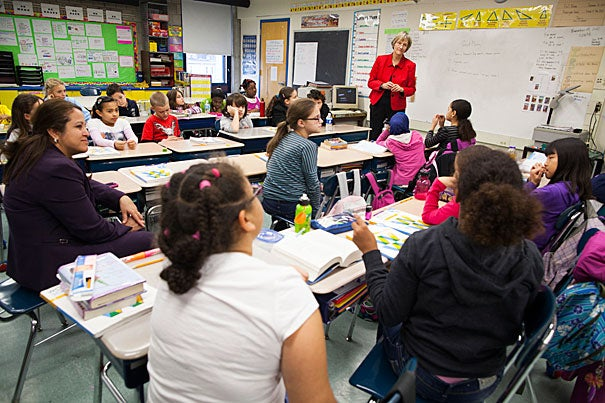 """President Drew Faust (standing at right) joined Maria Cordon, principal of the Hennigan Elementary School in Jamaica Plain on Tuesday as part of Boston's """"Principal for a Day."""" Faust shadowed Cordon (seated at left) on the principal's daily routine of morning announcements and classroom visits, and spoke to a fourth-grade class about the Civil War. The program, run by Boston Plan for Excellence in the Public Schools, brings business, civic, and educational leaders into the Boston public schools with the goal of inspiring partnerships with the schools. Harvard partners with the Hennigan in the areas of leadership and professional development, family engagement, after-school academic support, and science mentoring."""
