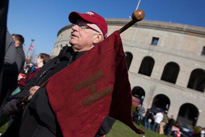 Bill Markus '60 strolled proudly through the tailgating party with the Little Red Flag of 1884.