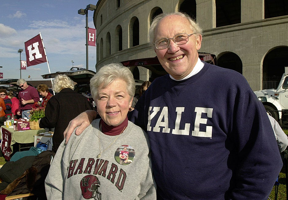 Dottie Balkema (left) and Milt Minkema display their divided loyalties before The Game in 2004. Dottie's grandson Robert Balkema '06 played linebacker for the Crimson, while Milt's son is a professor at Yale. Dottie and Milt are old friends who now see each other regularly after being married to different spouses. They first dated 50 years ago in high school.