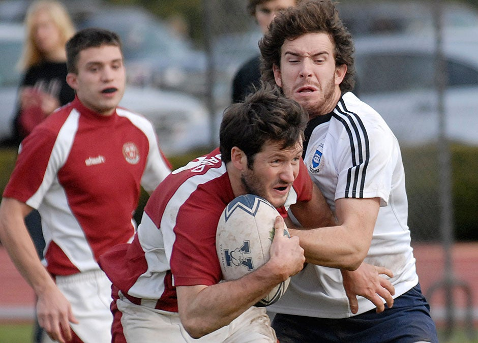 In 2009, a Harvard player struggles to score during the Harvard-Yale rugby match, which often precedes the football game. Established in 1872, the Harvard Rugby Football Club is one of the College's oldest athletic teams and the first rugby club in North America.