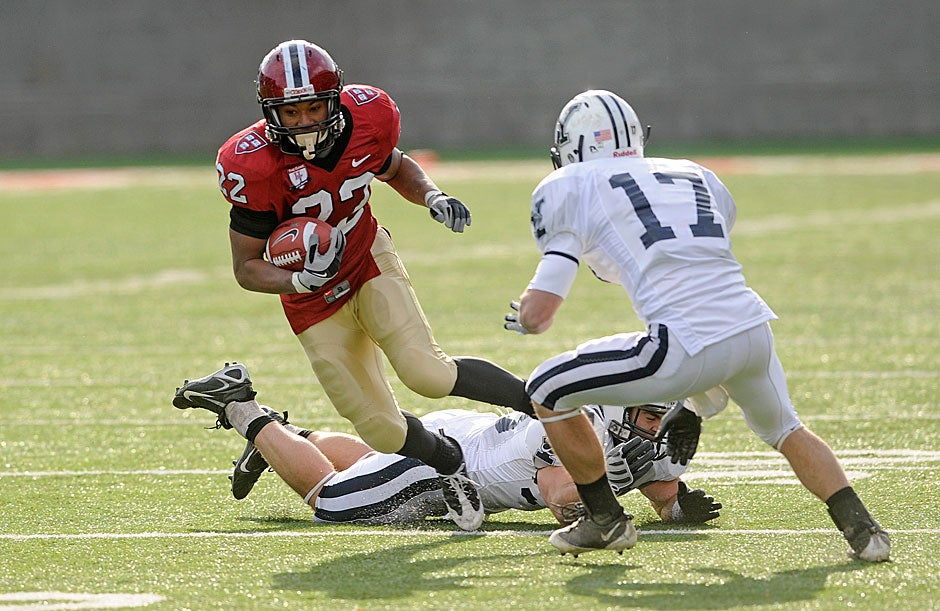 Crimson running back Gino Gordon '10 steps over a fallen Yale player as defensive back Adam Money moves in. Gordon gained 168 yards for the day in 2008 as the cold and wind forced Harvard to concentrate on its running game. Harvard won, 10-0, and clinched a share of the Ivy League title.