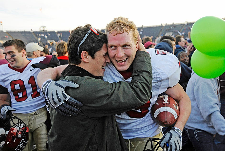 Crimson linebacker Conor Murphy '10 receives a well-deserved hug at game's end in 2009. Murphy holds the ball he recovered from a Yale fumble that ensured the victory as the clock wound down. Wide receiver Adam Chrissis '12 is at left.