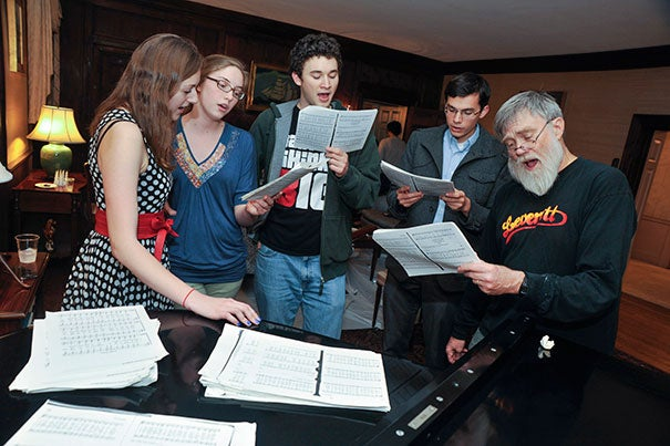 House Master Howard Georgi (right) joins student choristers for impromptu carols around the piano.
