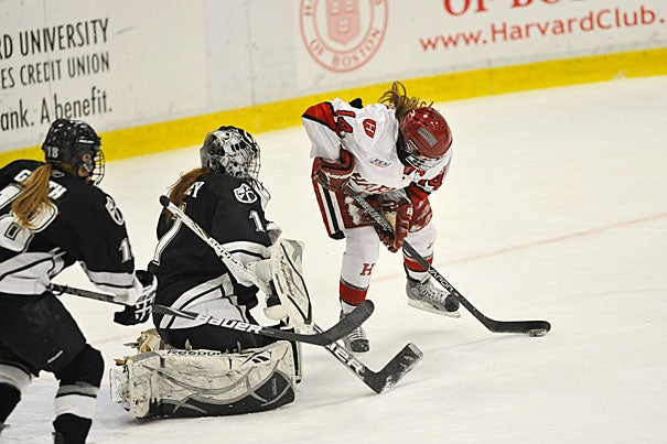 Co-captain Jillian Dempsey '13 maneuvers for a shot on goal as Providence College's goalie comes out of the crease. Dempsey finished with four goals to extend her point streak to 24 games. Harvard won, 8-1.