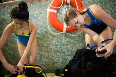 Jenny Chang '16 (left) and Ann-Marie Barrett '16 take off their gear after scuba training in the Malkin Athletic Center pool.